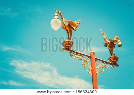 Twin of golden swan pole with blue sky and cloud with blue effect vintage style. General pole on street in Thailand with copy space for background.