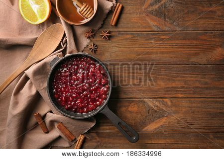 Delicious cranberry sauce in pan on wooden background