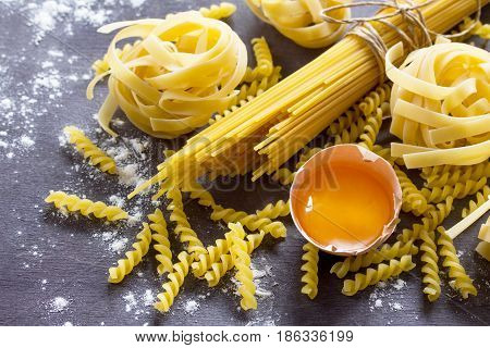 Various Types Of Pasta Spaghetti, Fusilli, Fettuccine And Raw Egg Yolk On A Kitchen Wooden Table. Co