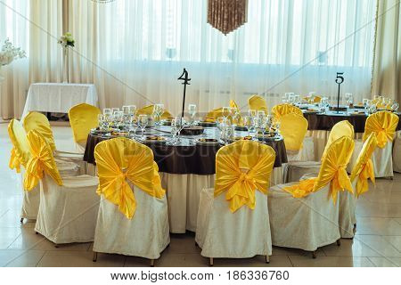 Chairs With Yellow Cloth And Table For Guests Served For Wedding Banquet With Numbers. Dinner Table
