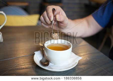 Man Puts Sugar Into a Coffee Cup on cafe