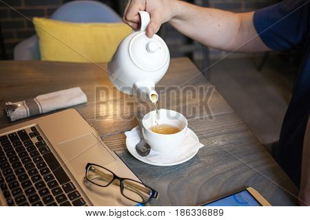 Man drinking tea in cafe with mobile phone on the table