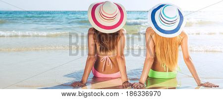 Tropical vacation. Two young women sitting on the beach and looking at sunset. Banner crop for copy space.