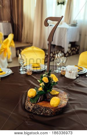 Wedding Flower Arrangement Of Yellow Roses, Greenery And Lemons On Stump Under Table Number Card On
