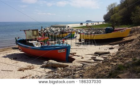 Gdynia, Poland - May 14, 2017: Empty fishing boats on the beach. In the background people walk on the boulevard