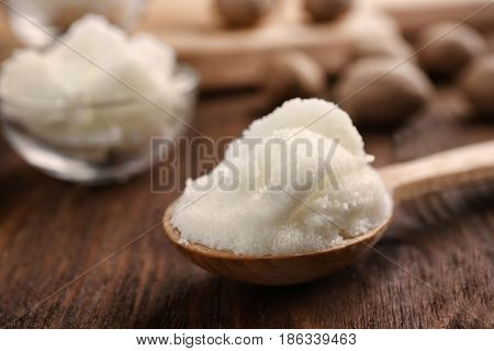 Shea butter in spoon on wooden background, close up