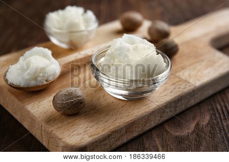 Shea butter in bowl and spoon on wooden background