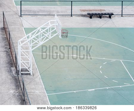 Empty basketball field with the metal hoop in the center area of the urban condominium.