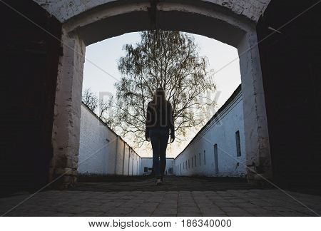 The girl enters the open gate against the background of a growing tree. Russia