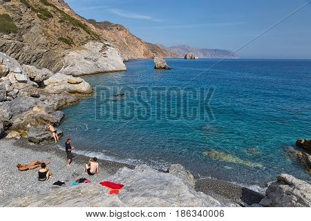 Amorgos Island Greece - October 2015: Company of young people on the beach of a Greek Island Amorgos