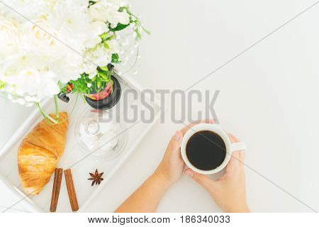 Hands holding cup of coffee - breakfast scene with copy space