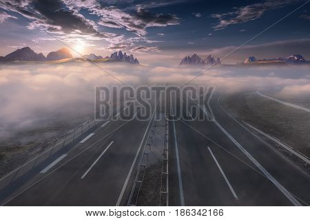 Open highway to the mountain range towards the rising sun. Straight motorway in beautiful misty landscape.