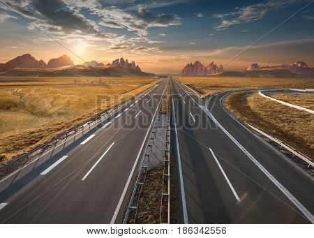 Open highway to the mountain range towards the setting sun. Straight freeway in beautiful desert landscape.