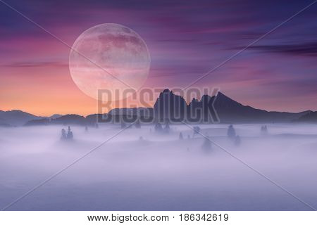 Super moon over the mystical mountain landscape covered with fog at beautiful sunrise.