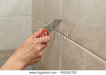 Male hands with knife removing the old grout. Replacing old grout between tiles. Raking out tiles for regrouting.