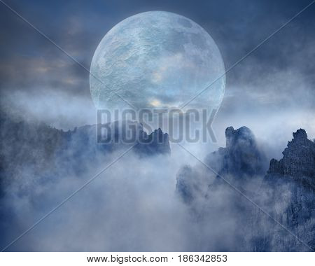 Super moon over the mystical mountain landscape covered with fog. Spooky fantasy scenery.
