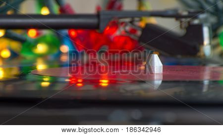 A turntable playing music vinyl record. Colorful lights blurred in background with reflections at the vinyl.