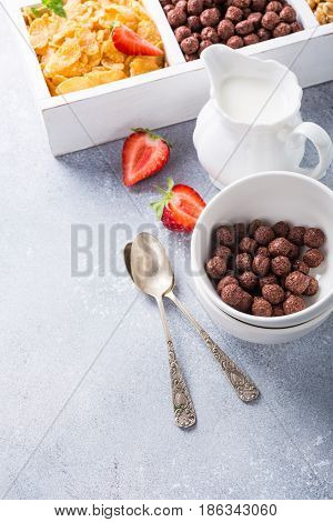 Milk jug and variety of cold quick breakfast cereals with berries in white wooden box, healthy eating concept, selective focus, copy space.