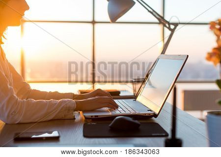 Female teleworker texting using laptop and internet, working online. Freelancer typing at home office, workplace