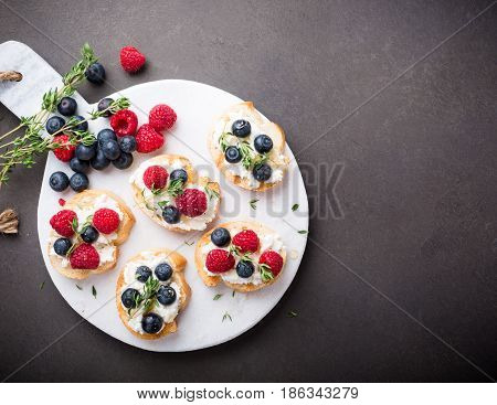 Sandwiches with fresh berries, goat cheese and honey on marble cutting board, top view, copy space.