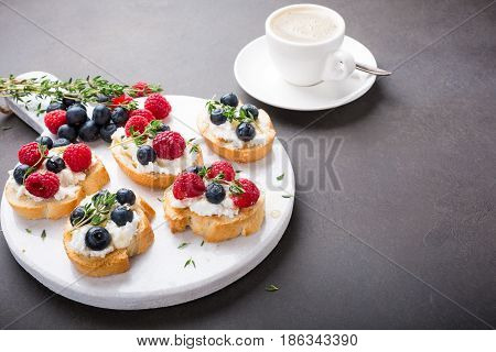Cup of coffee with berry and goat cheese sandwiches on marble cutting board, top view, copy space.