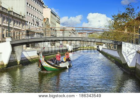 AVEIRO PORTUGAL - MARCH 21 2017: Traditional boat and tourists in Vouga river Aveiro Portugal on March 21 2017