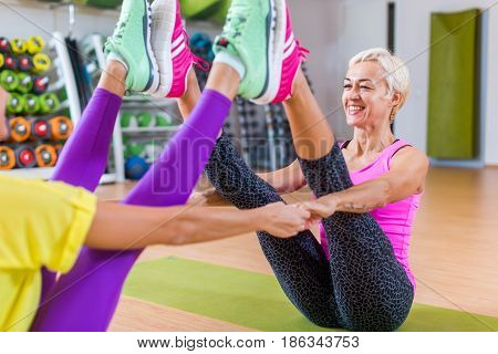 Mid-aged woman working out in pairs on mats in a gym. Woman in sportswear doing yoga buddy boat pose with partner.