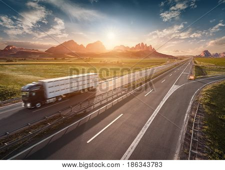 Lone truck driving from the mountain range towards the rising sun. Fast motion drive on the straight freeway in beautiful landscape. Transportation concept.