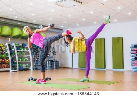 Two athletic women working out in gym, doing sidekicks exercise strength training