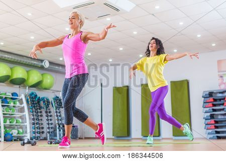 Sporty ladies doing aerobic dance exercises. Two female athletes enjoying weight loss group cardio workout in gym.
