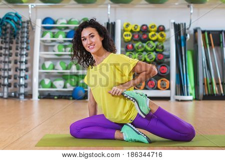 Attractive brunette young woman sitting on mat warming-up before training stretching her quadriceps in gym smiling and looking at camera.