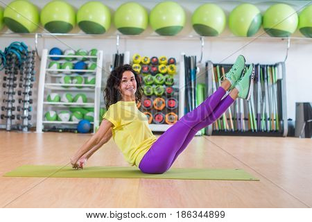 Pretty fitness model doing scissors exercise sitting on floor crossing and uncrossing straight legs smiling and looking at camera.