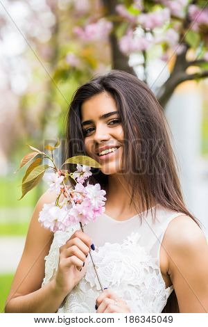 Joyful Positive Caucasian Woman Posing With Flowering Sakura Tree.