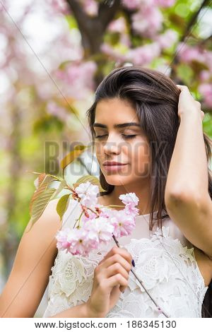 Young Positive Woman Sniffs The Branch Of Sakura. Beauty And Nature.