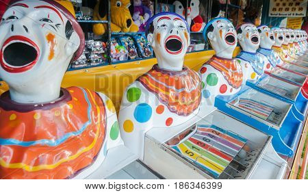 A row of sideshow carnival game clowns with mouths open diminishing into distance.