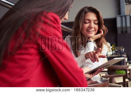 Over-the-Shoulder Shot of two glorious business women looking photos on tablet while having rest with cup of coffee
