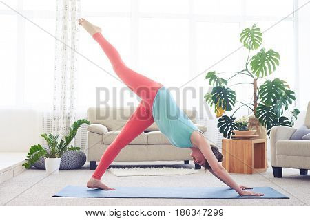 Wide shot of nice sportswoman being in one-legged downward-facing dog asana