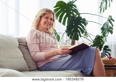 Mid shot of gorgeous adult woman smiling while reading book