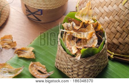 Fried crispy sun dried fish over green banana leaf.
