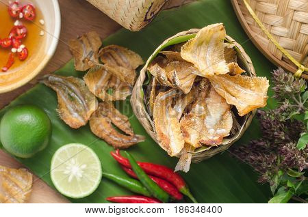 Fried crispy sun dried fish over green banana leaf. Asian food decorated with organic kitchen garden.