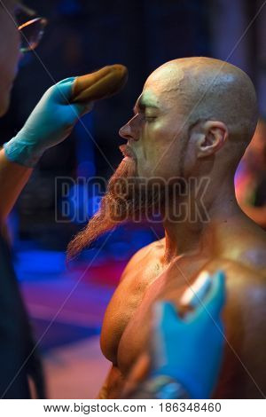 Bodybuilding competition backstage: contestant being oiled and fake tan applied to skin. selective focus.
