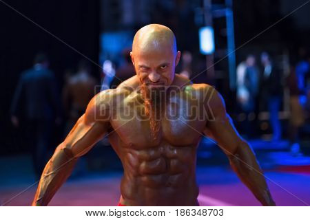 Bodybuilding contest behind the scenes: the contestant is preparing for the performance. Selective focus.