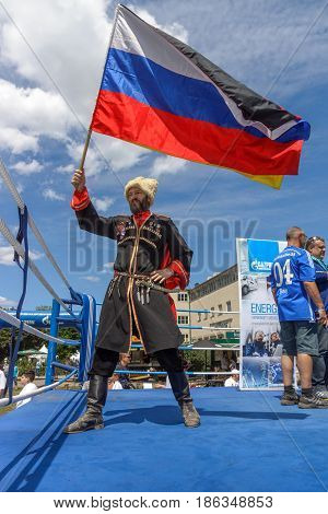 BERLIN - JUNE 11 2016: Russian Cossack with the Russian flag. German-Russian festival devoted to the Independence Day of Russia. District Karlshorst East Berlin.