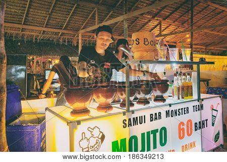 Khao Lak, Thailand - December 27, 2015: Mobile mini bar at night market and smiling barman who makes the Mojito cocktail