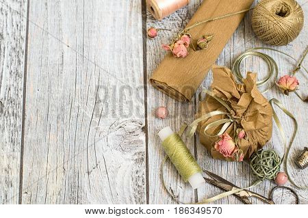 Creativity Packing gifts in vintage style with the use of natural materials.  Paper, decorative tape, dried flowers, threads and scissors on a gray wooden background. Selective focus.