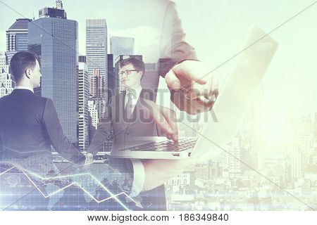 Two handsome young men shaking hands and using laptop on abstract city and forex chart background. Online business. Double exposure
