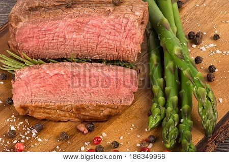 Close up on fillet mignon with asparagus on the side.