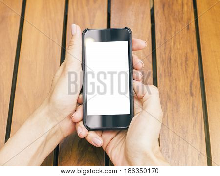 Top view of girl's hands holding empty white cellular phone above wooden table. Mock up