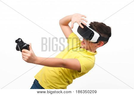 Little boy in VR headset holding joystick and looking scared isolated on white background.