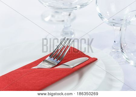 Elegant table setting in the restaurant: cutlery in a red napkin on the plates and next to the wine glasses